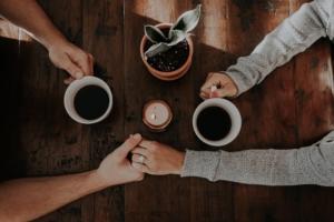 par der holder i hånd og drikker kaffe